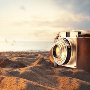 vintage-photo-camera-on-the-sand-at-the-beach